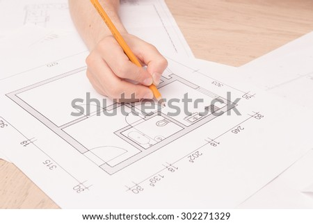 Real engineer. Close up of young husband holding pencil and making drawings of his new flat on the floor