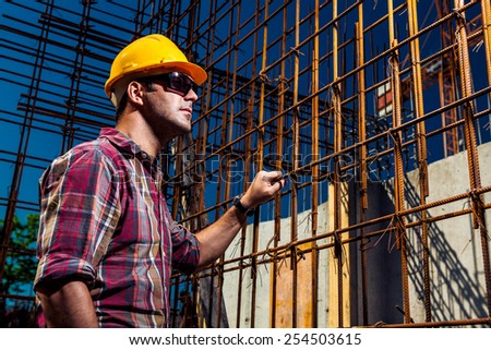 Real Engineer wearing protective gear and sunglasses supervising his construction site near reinforced steel concrete - stock photo