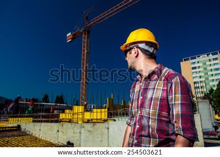 Real Engineer wearing protective gear and sunglasses supervising his team of construction workers on site - stock photo