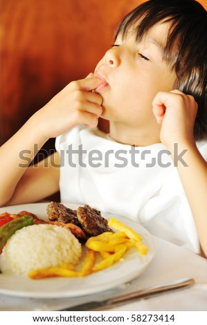 Real enjoying food, cute kid with finger in his mouth - stock photo
