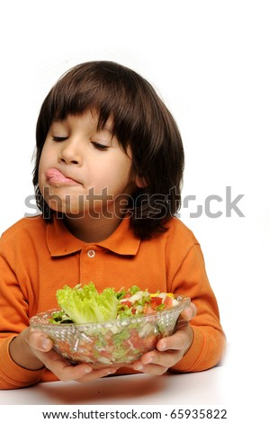 Real enjoying fresh green salad, cute kid with tongue out of his mouth - stock photo