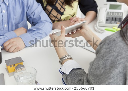 Real estate agent and visitor's young couple - stock photo