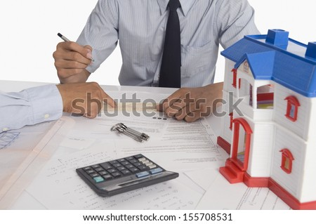 Real estate agent discussing a document with a customer - stock photo