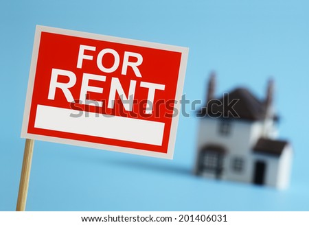 Real estate agent for rent sign with house in background - stock photo