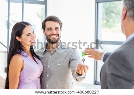 Real-estate agent giving house keys to couple in their new home - stock photo