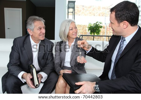 Real-estate agent giving house keys to senior couple - stock photo