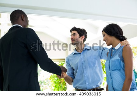 Real estate agent giving house keys to the couple at home