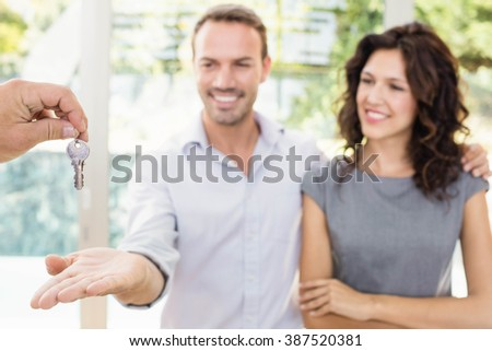 Real-estate agent giving keys to new property owners - stock photo