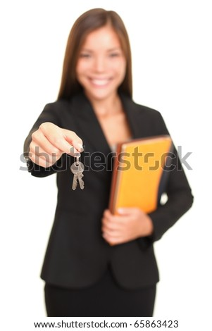 Real estate agent giving keys. Young realtor smiling handing over house keys to the new house owner, focus on keys. Isolated on white background. - stock photo