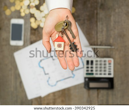 Real estate agent handing over a house key, desktop with tools, wood swatches and computer on background, top view - stock photo