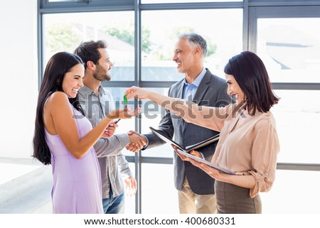 Real estate agent handing over house key to young couple in their new home - stock photo
