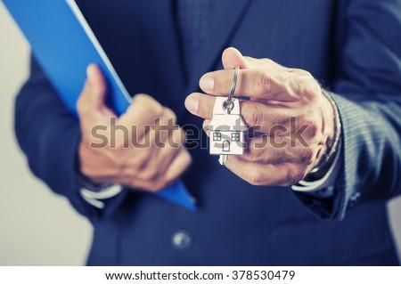 Real estate agent handing over house keys  - stock photo