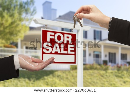 Real Estate Agent Handing Over the House Keys in Front of a Beautiful New Home and For Sale Real Estate Sign. - stock photo