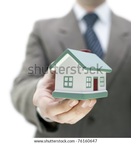 Real estate agent holding a toy house - stock photo