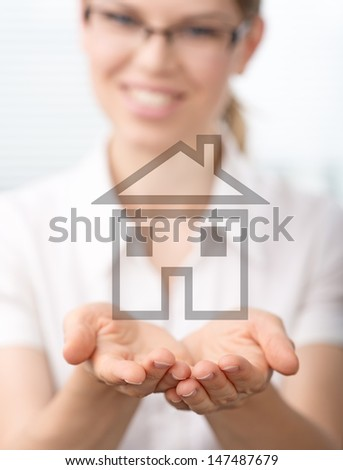 Real estate agent holding illustrated house in her hands. Portrait of young smiling female mortgage consultant.  - stock photo