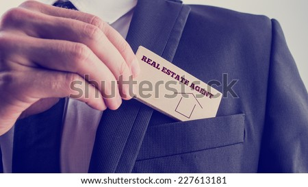 Real Estate Agent in Black Suit Putting Small Wooden Piece with Real Estate Agent Text and Graphic to Front Pocket. - stock photo