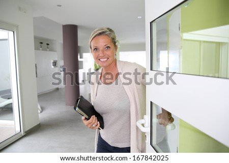 Real-estate agent presenting modern house - stock photo