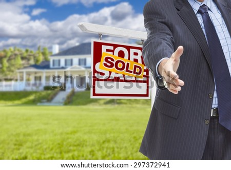 Real Estate Agent Reaches for Handshake with Sold Sign and New House Behind. - stock photo