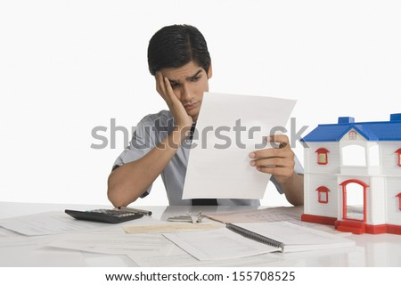 Real estate agent reading a document near a model home - stock photo