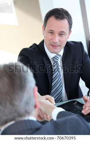 Real-estate-agent shaking hand to new property owner - stock photo
