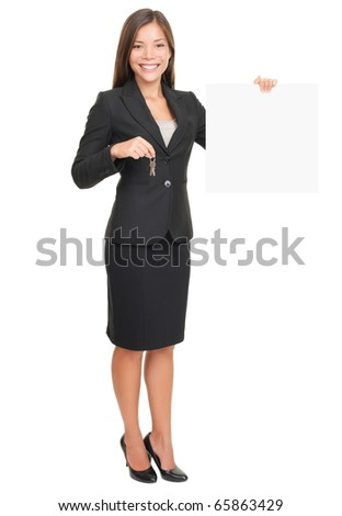 Real estate agent showing blank sign while holding house keys. Beautiful smiling woman (mixed Caucasian / Asian) isolated on white background in full body. - stock photo