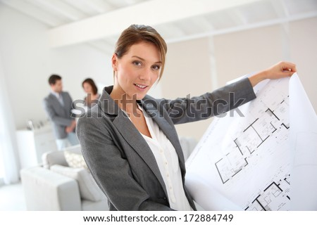 Real estate agent showing construction blueprint - stock photo