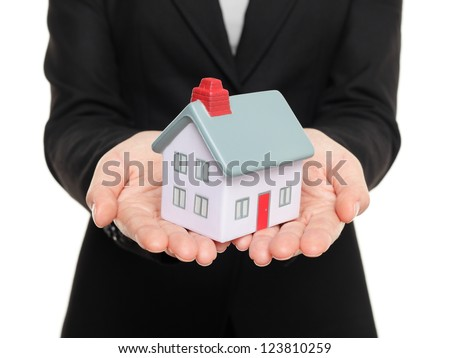 Real estate agent showing mini house / home closeup of female realtor hands showing miniature model house isolated on white background. - stock photo