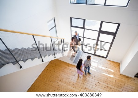 Real estate agent showing new house to couple - stock photo