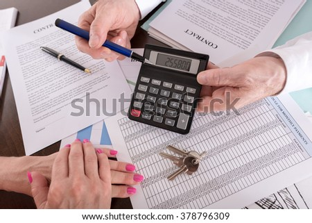 Real estate agent showing the purchase price on a calculator to his client (random english dummy text used)
