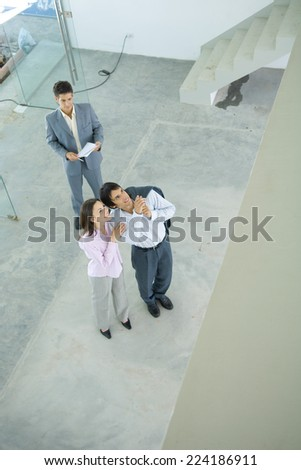 Real estate agent showing unfinished house to enthusiastic young couple, high angle view - stock photo
