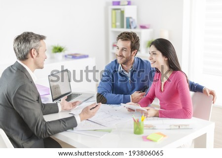 real-estate agent shows a build project  to a young couple - stock photo