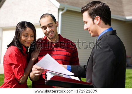 Real Estate: Agent Shows Information To Couple - stock photo