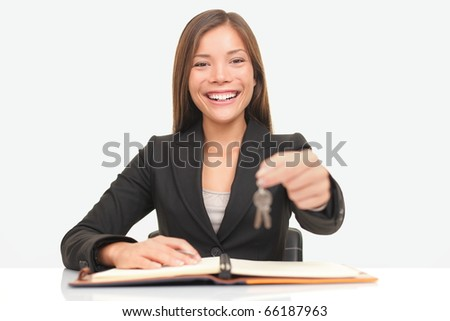 Real estate agent sitting at desk giving house keys smiling to new home owners. - stock photo
