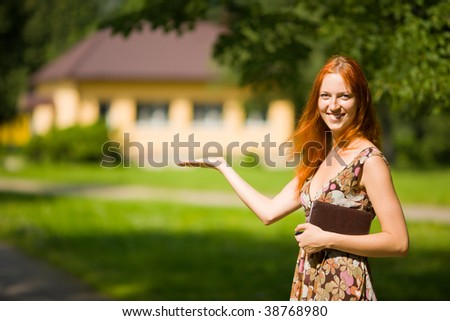 Real Estate Agent smiles near new house for sale - stock photo