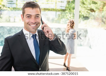 Real-estate agent talking on the mobile phone and client looking at the apartment - stock photo