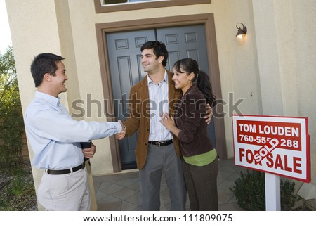 Real estate agent with couple buying new house - stock photo