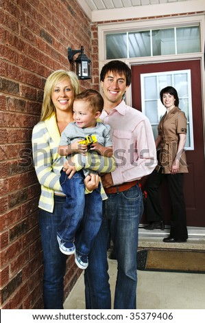 Real estate agent with family welcoming to new home - stock photo