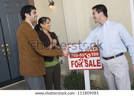 Real estate agent with hispanic couple buying new house - stock photo