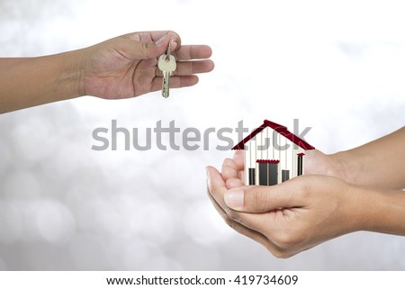 Real estate agent with house model and keys on green backgrounds