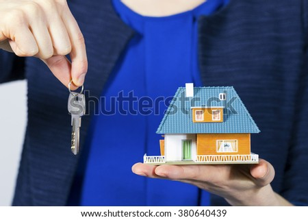 real estate agent with key and house model on hand - stock photo
