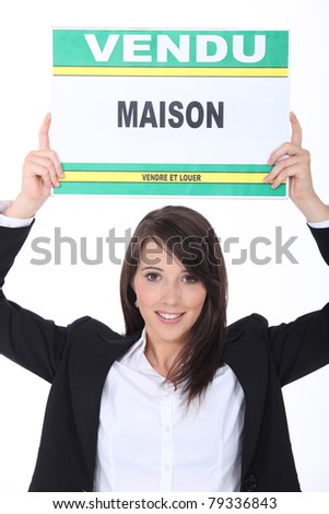 Real estate agent with sold house sign - stock photo
