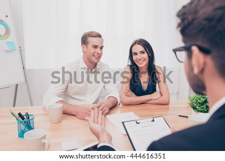 Real estate agent working with couple of customers in the office - stock photo