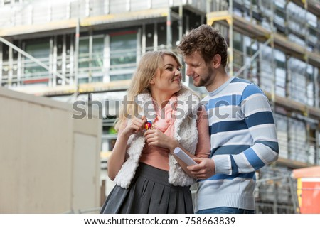 Real estate and family concept - young couple on front of new big modern house construction site with keys dreaming about home