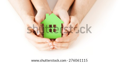 real estate and family home concept - closeup picture of male and female hands holding green blank paper house - stock photo