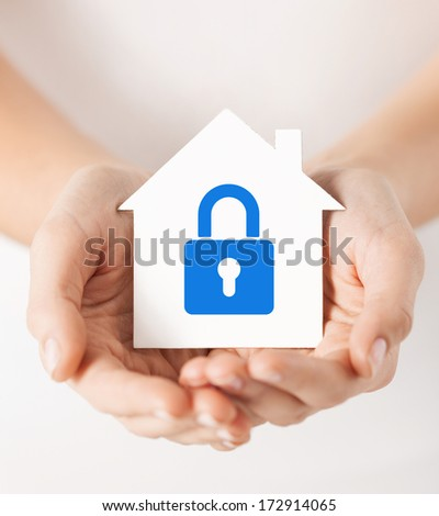 real estate and family home security concept - closeup picture of female hands holding white paper house with blue lock - stock photo