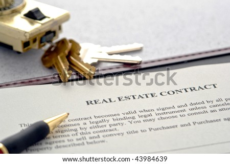 Real estate broker sale contract for house resale agreement with ink pen and house keys on a Realtor key holder lock box (fictitious document with authentic legal language)  - stock photo