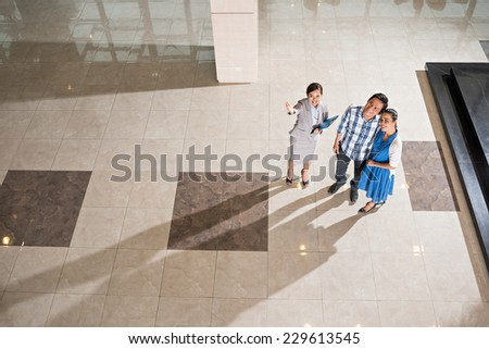 Real-estate broker showing new house to the couple, view from above - stock photo