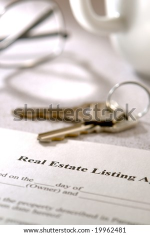 Real estate brokerage home listing contract agreement and set of house keys on a kitchen table - stock photo