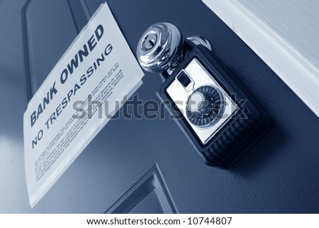 Real estate combination lock box on foreclosed house door with bank owned lender foreclosure notice (fictitious document with authentic legal language) - stock photo