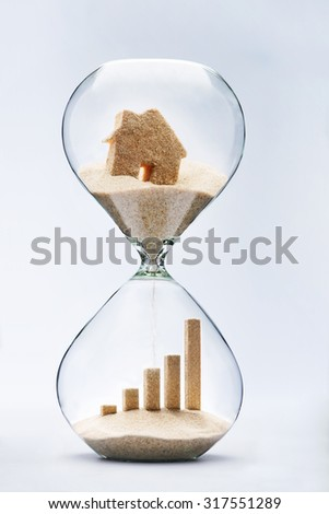 Real estate concept. Business growth graphic bar made out of falling sand from house flowing through hourglass - stock photo